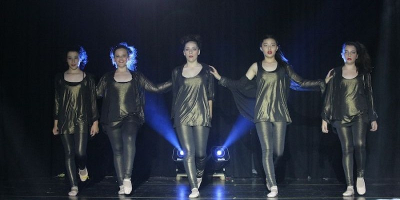 Five young girls performing at a dance concert