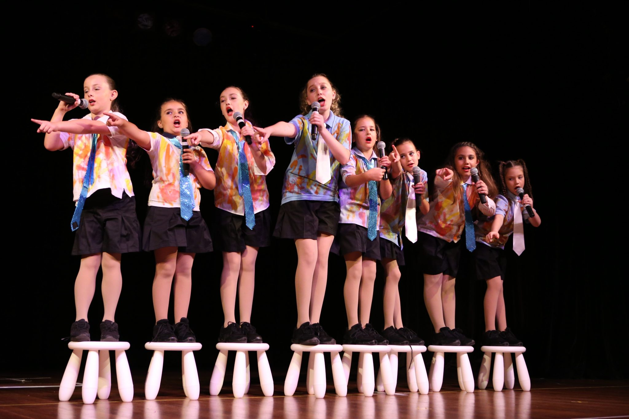 Young performers singing at dance concert