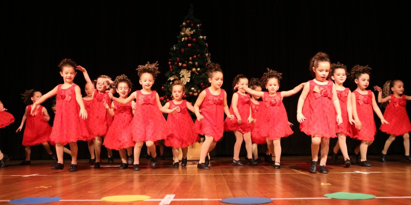 Toddlers in red dresses performing in a dance concert