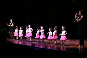 9 pre-school aged girls in pink skirts dacing with two teachers dressed in black
