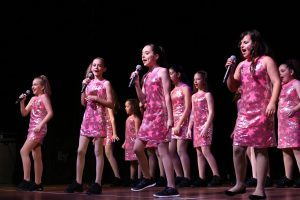 A number of girls dressed in Pink sing into microphones