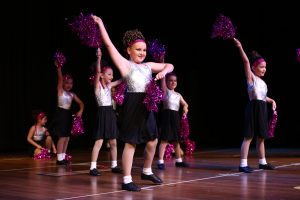 Young girls dressed as cheerleaders dance for an audience