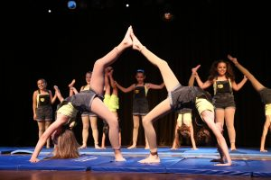 Two young girls perform a difficult yoga pose in concert