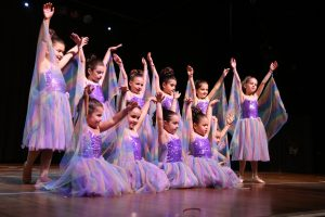 Young girls, dressed as purple fairies strike a pose at dance concert
