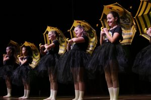 Young girls with bee umbrellas dance