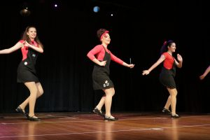 Three girls in black overalls tap dance at concert.