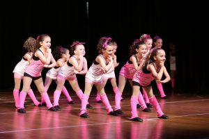Toddler girls, in pink and white, dance