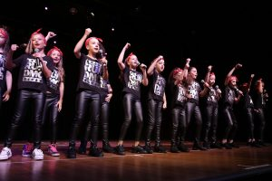 Young girls in black RUN DMC t-shirts, sing and dance