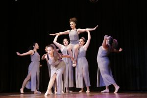 A graceful classical ballet performance by seven teenage girls with one girl on the shoulders of two others