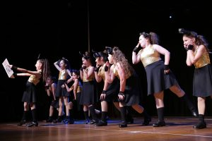 A large number of young girls in black and gold dance