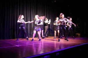 Eight teenage girls dressed in black dance