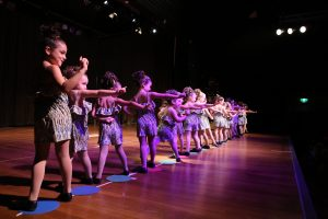 A large number of young girls standing left to right strike up a dance move