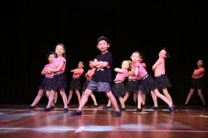 A young boy dressed in black dances in the foreground while in the backgroun a large number of girls in pink dance