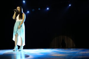A pretty young girl with a blue skirt sings