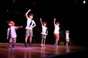 Five young boys perform hip hop moves to crowd
