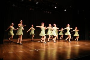 Girls in green dresses dancing in concert