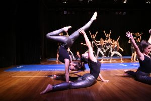 Two girls in the foreground perform difficult yoga pose while in the back ground more kids also perform yoga moves