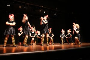 A large number of girls dressed up as bees dancing in a concert recital