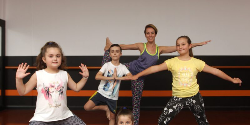 Young children performing yoga with teacher