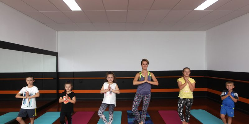 Students practicing yoga with teacher